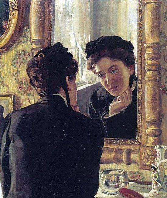 Девушка смотрит а свое отражение в зеркале